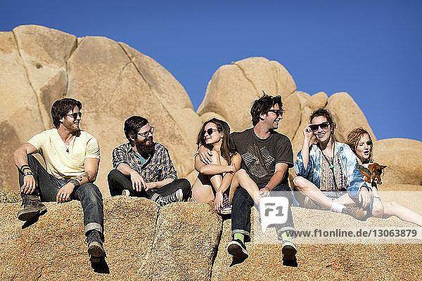 Tiefwinkelansicht von Freunden  die auf einer Felsformation vor klarem Himmel sitzen