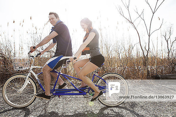 Side view of couple riding tandem bicycle against sky