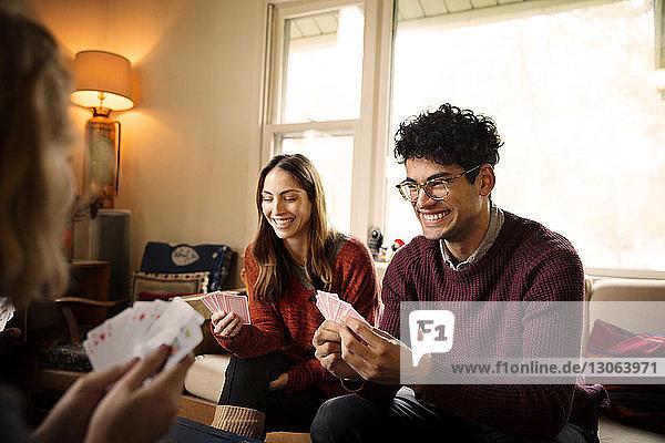 Fröhliche Freunde spielen Karten  während sie sich im beleuchteten Wohnzimmer ausruhen