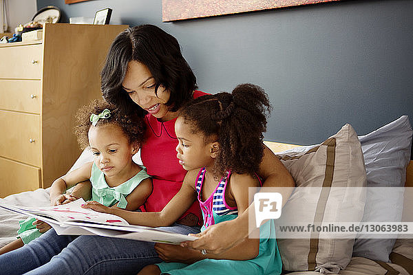 Mother looking in book with children while sitting on bed at home