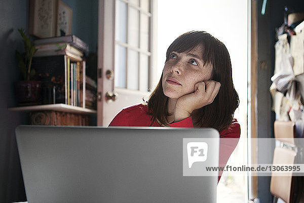 Woman with hand on chin looking away while sitting at home