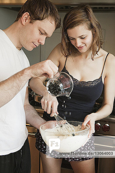 Couple preparing cake batter while standing in kitchen