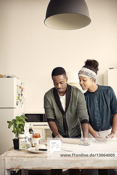Frau sieht Mann beim Teigrollen am Küchentisch
