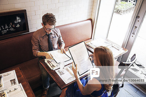 High angle view of couple reading menu while sitting in restaurant