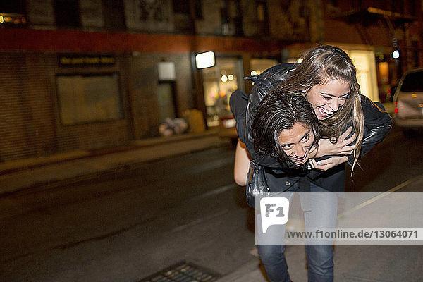 Glücklicher Mann nimmt seine Freundin huckepack  während er nachts auf einem Fußweg geht