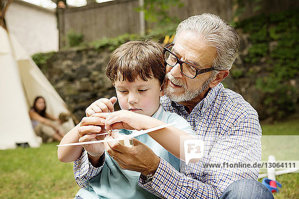 Boy playing with grandfather in lawn
