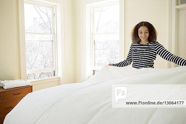 Glückliche Frau legt zu Hause eine Decke aufs Bett