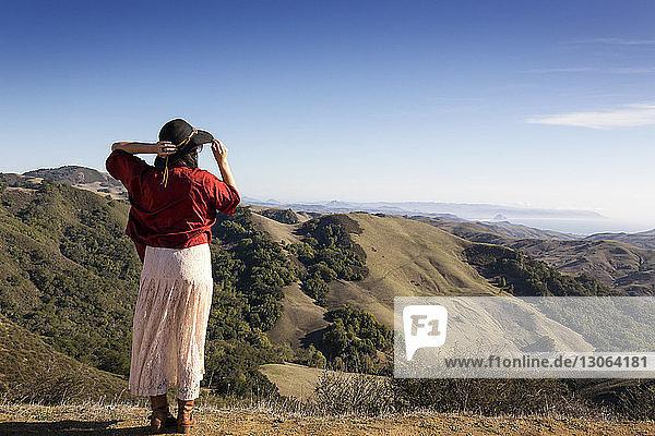 Rückansicht einer Frau  die auf einem Berg steht und auf die Aussicht schaut