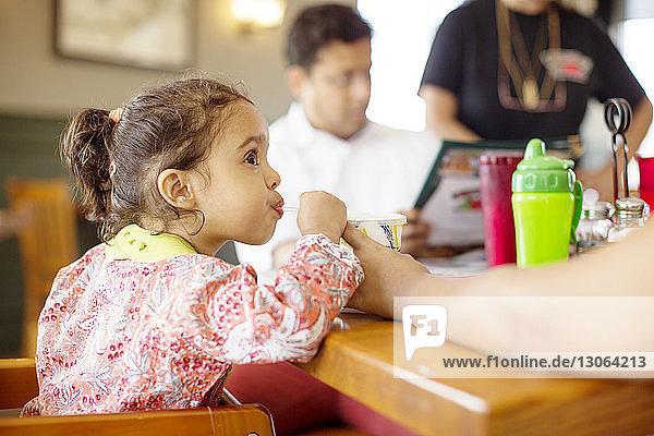 Mädchen trinkt Saft  während sie im Restaurant beim Vater sitzt