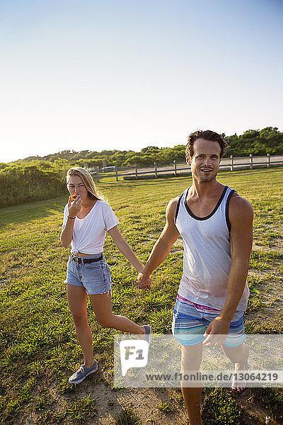 Paar hält sich beim Gehen auf dem Feld gegen den klaren Himmel an den Händen