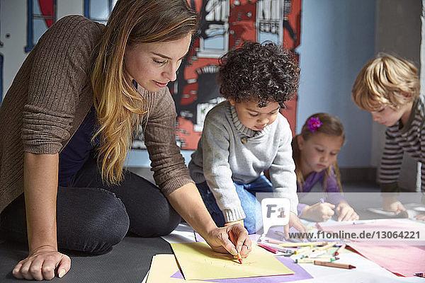 Lehrer beim Zeichnen von Arbeiten mit Vorschulkindern