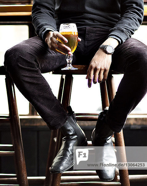 Low section of man holding wineglass while sitting on stool in bar
