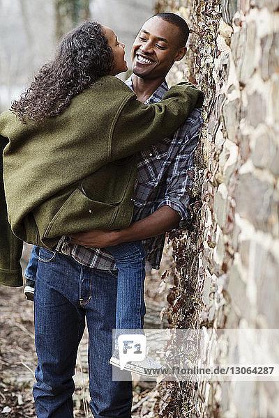 Glücklicher Vater trägt Tochter  während er an der Wand steht