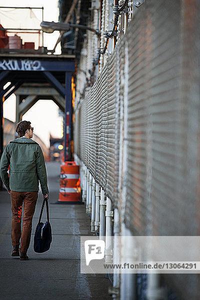 Rückansicht eines Mannes  der auf dem Fußgängerweg der Manhattan Bridge geht