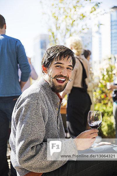 Porträt eines fröhlichen Mannes  der während einer Gartenparty ein Rotweinglas hält