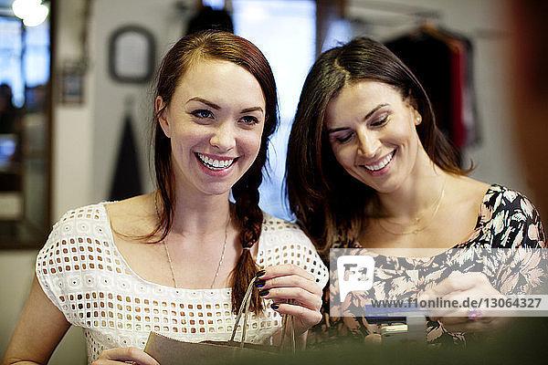 Glückliche Besitzer mit Kreditkarte und Einkaufen im Geschäft