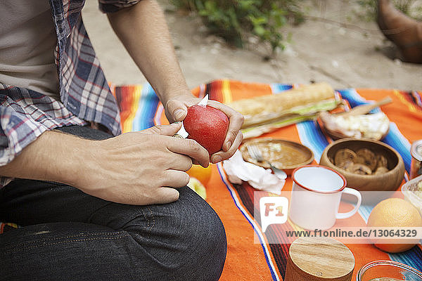 Nahaufnahme eines Mannes  der auf dem Feld sitzend Obst schneidet