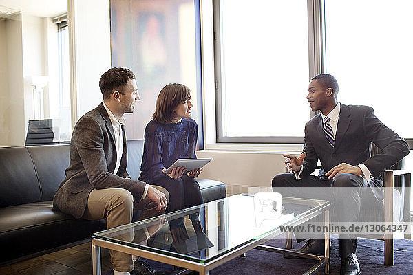 Geschäftsleute diskutieren  während sie im Büro sitzen