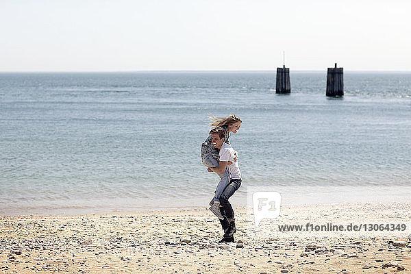 Mann hebt Freundin hoch  während er am Strand steht