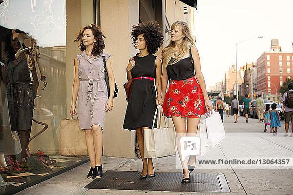 Schaufensterbummel in voller Länge von Freunden beim Spaziergang auf dem Bürgersteig in der Stadt