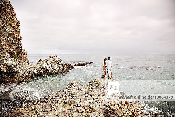 Rückansicht eines auf einem Felsen am Strand stehenden Paares