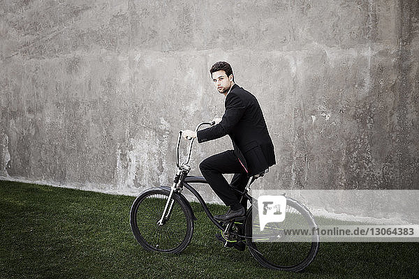 Portrait of man riding bicycle on grassy field