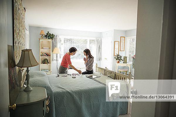 Frauen betrachten Schmuckstücke  während sie auf dem Bett sitzen