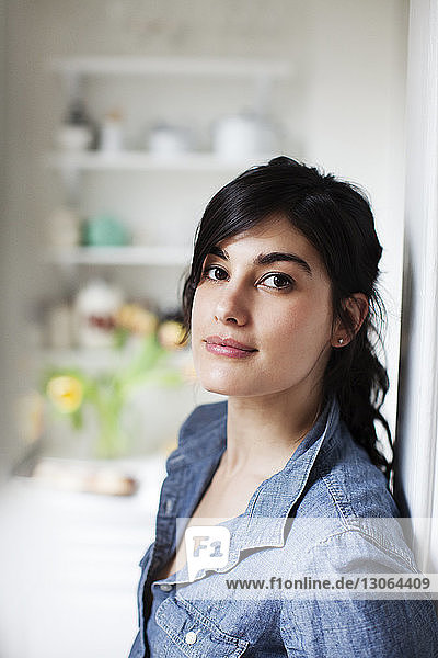 Portrait of confident woman leaning by wall at home