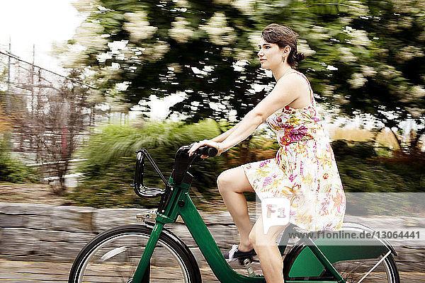 Frau fährt Fahrrad auf der Straße in der Stadt