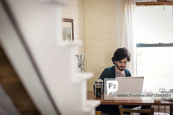 Mann benutzt Laptop-Computer  während er zu Hause sitzt