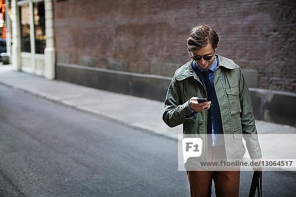 Mann benutzt Mobiltelefon  während er auf der Straße steht