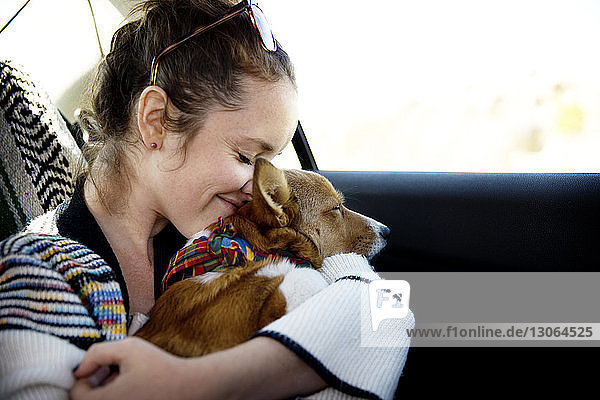 Woman embracing dog while sitting in car