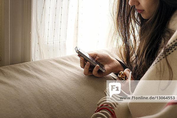Ausgeschnittenes Bild einer Frau  die zu Hause ein Smartphone benutzt