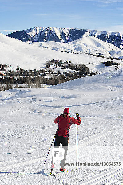 Rückansicht einer Frau beim Skifahren auf schneebedecktem Feld