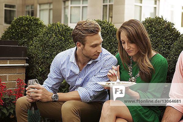 Mann sieht Frau beim Essen an  während er auf dem Sitz sitzt