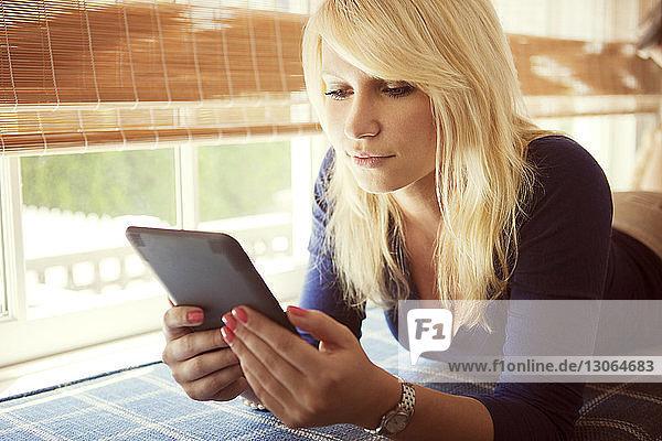 Frau benutzt Tablet-Computer im Liegen zu Hause
