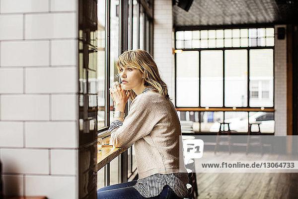 Frau schaut weg  während sie in der Bar sitzt