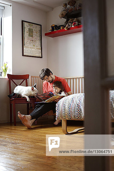 Father and daughter reading book while sitting with dog at home