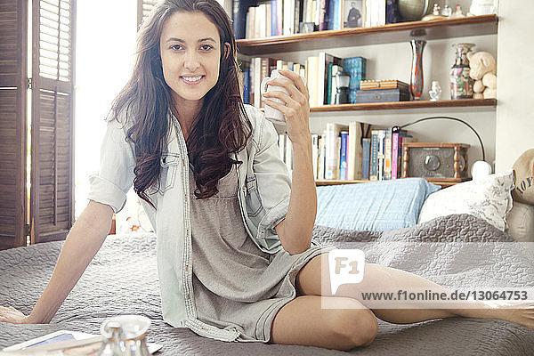 Porträt einer Frau  die eine Kaffeetasse auf dem Bett hält