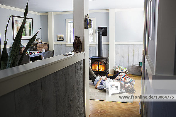 Couple relaxing on floor in living room at home