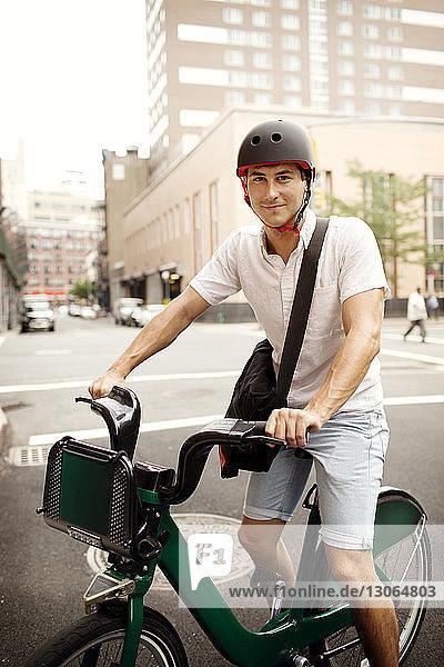 Porträt eines Mannes mit Fahrrad auf der Straße