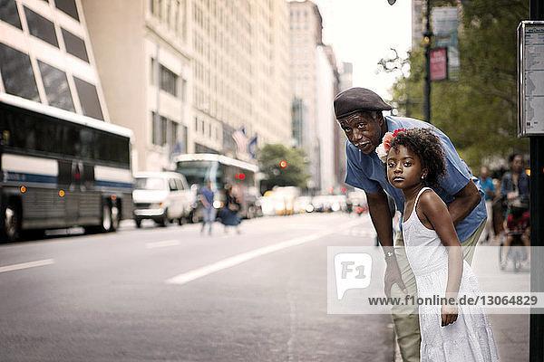 Großvater und Enkelin stehen auf dem Bürgersteig in der Stadt