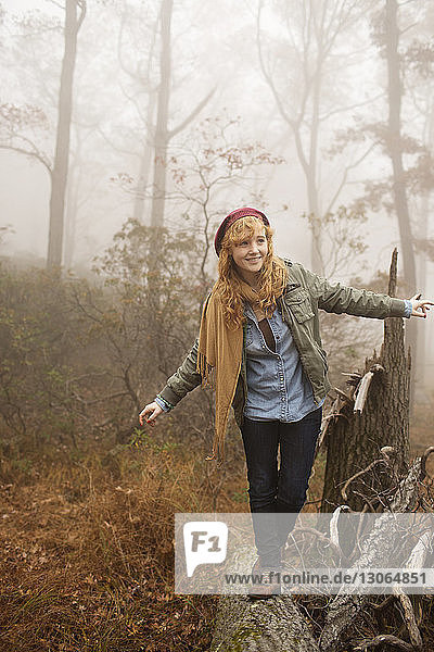 Woman looking away while walking on fallen tree trunk in forest