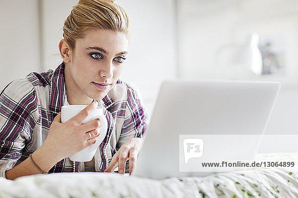 Frau hält Becher mit Laptop zu Hause