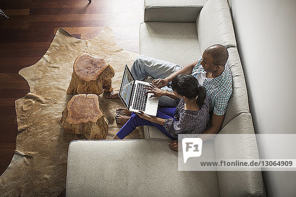 High angle view of couple using laptop computer while sitting on sofa at home