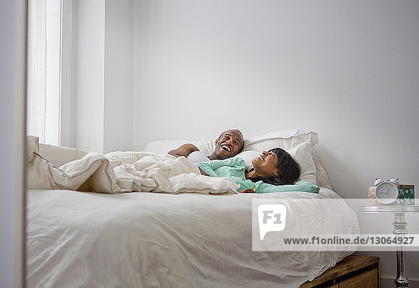 Cheerful couple in bed at home