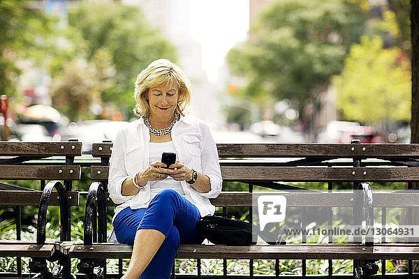Glückliche Frau benutzt Mobiltelefon  während sie in der Stadt auf einer Bank sitzt