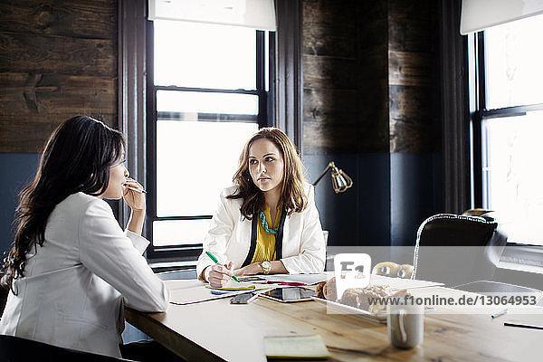 Geschäftsfrauen diskutieren  während sie im Büro am Schreibtisch sitzen