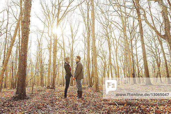 Side view of couple holding hands while standing in forest
