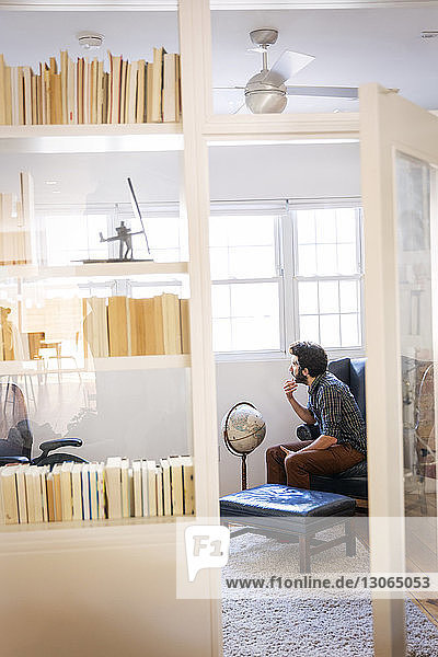 Thoughtful man sitting in library at home
